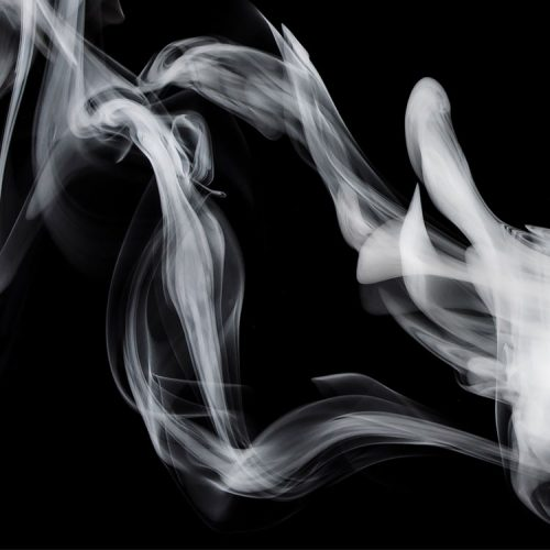 Photo of cigarette smoke rising into the air